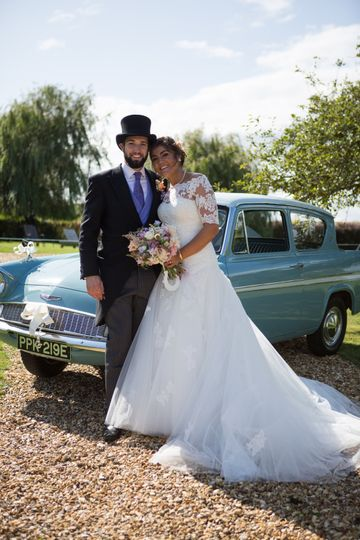 Bride and groom by car