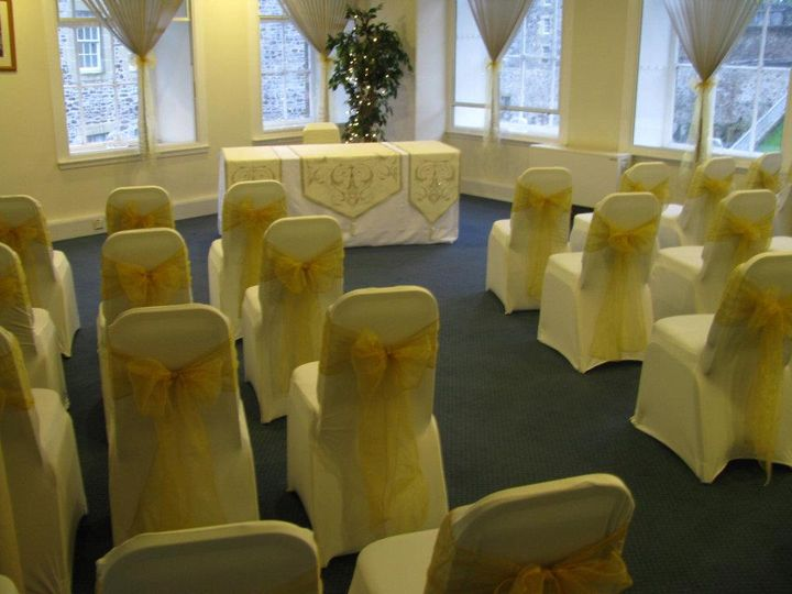 Ivory chair covers with gold sashes