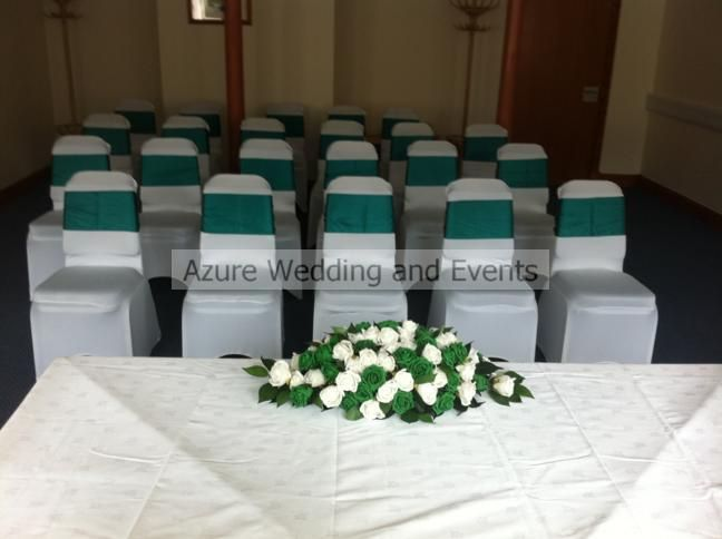 White chair covers with emerald green satin sashes, top table flower