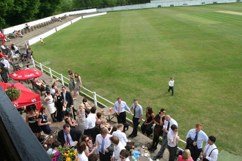 Wedding guests have drinks on the terrace